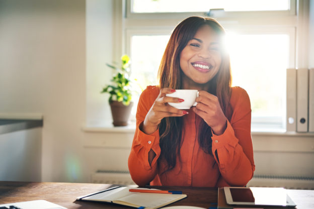 Smiling young woman drinking a coffee in her home office